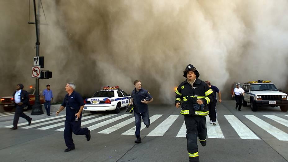 Bombeiros e policiais fogem da nuvem de poeira provocada pela queda de uma das torres do World Trade Center, 11 de setembro de 2001 em Nova York