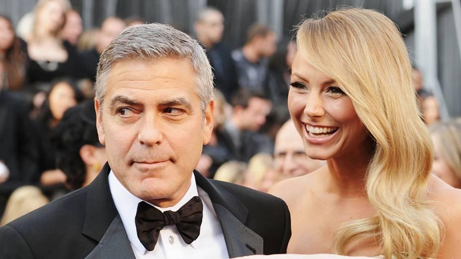 Ao lado da namorada Stacy Keibler, George Clooney brinca com fotógrafo