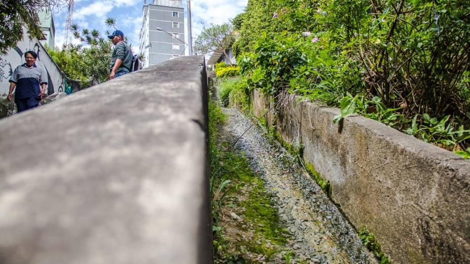 <p>Ao lado da escadaria que liga a Rua Werner Sack à Rua Orós está uma das nascentes do Rio das Corujas. Os vigias que trabalham na guarita ao pé do morro garantem que a água jorra 24 horas por dia, 365 dias por ano</p>