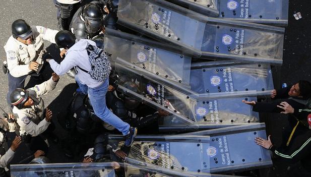 Manifestante pula por cima de cordão de policiais em Caracas durante protesto contra o governo Maduro