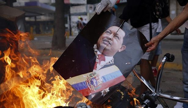 Manifestante queima foto do ex-presidente Hugo Chávez em Caracas