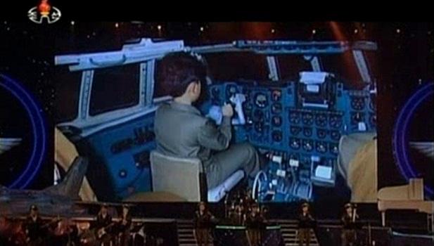 O pequeno ditador: telão mostra Kim Jong-un durante sua infância. Nesta imagem ele está dentro da cabine de um avião