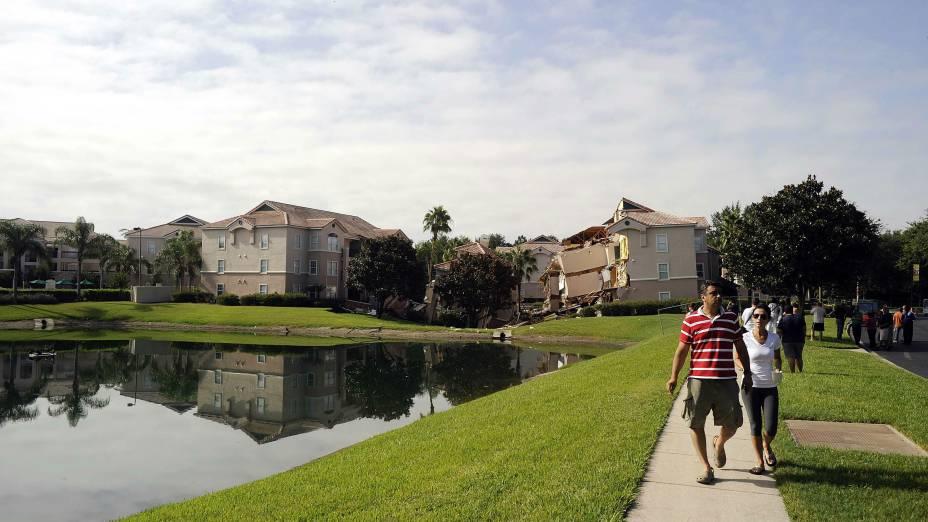 Pessoas caminham perto do local onde um buraco se abriu, levando construções ao chão, em região perto dos parques da Disney, na Flórida