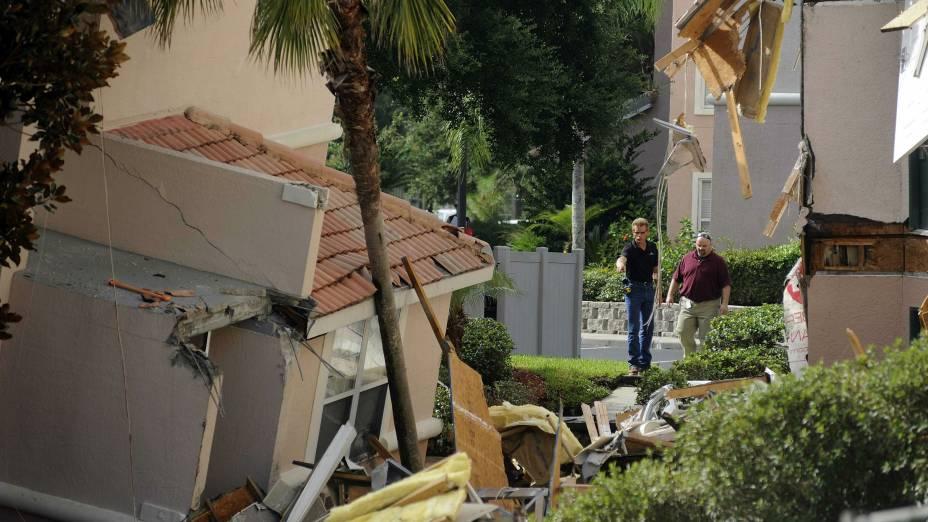 Homens observam buraco que provocou a queda de construções em região perto dos parques da Disney