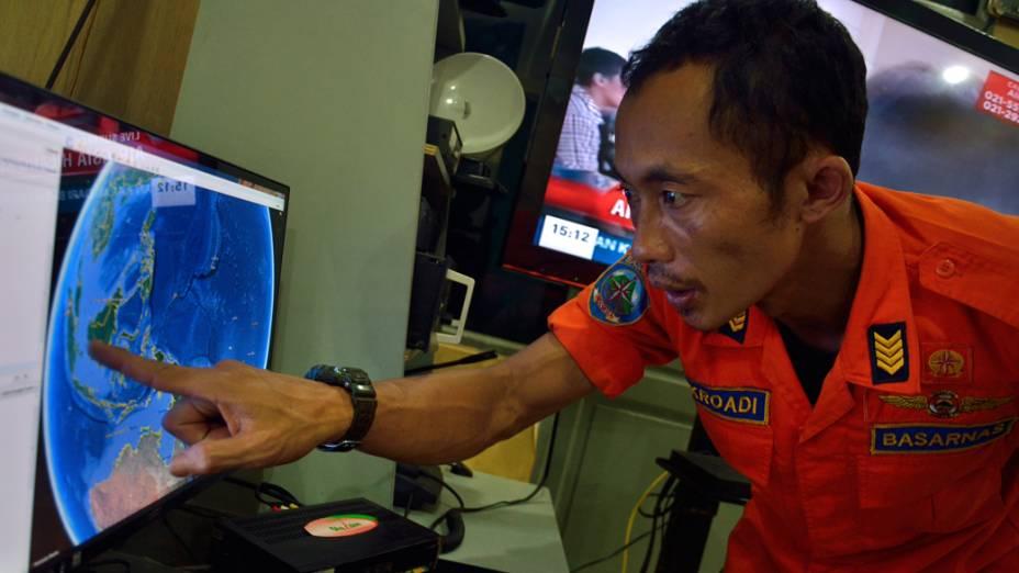 Oficial da Agência Nacional de Busca e Resgate da Indonésia aponta a posição onde a aeronave desapareceu