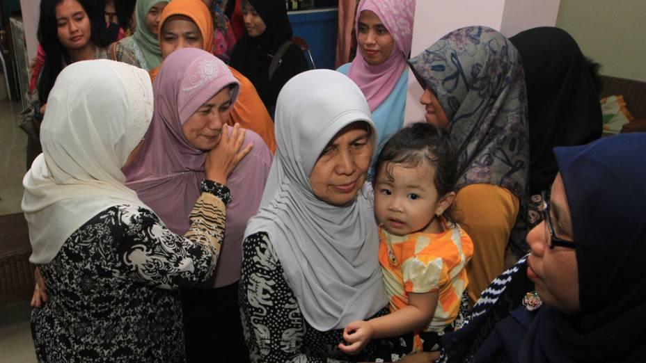 Familiares de passageiros do voo QZ-8501 da AirAsia no Aeroporto Internacional de Juanda, em Surabaya, Java Oriental