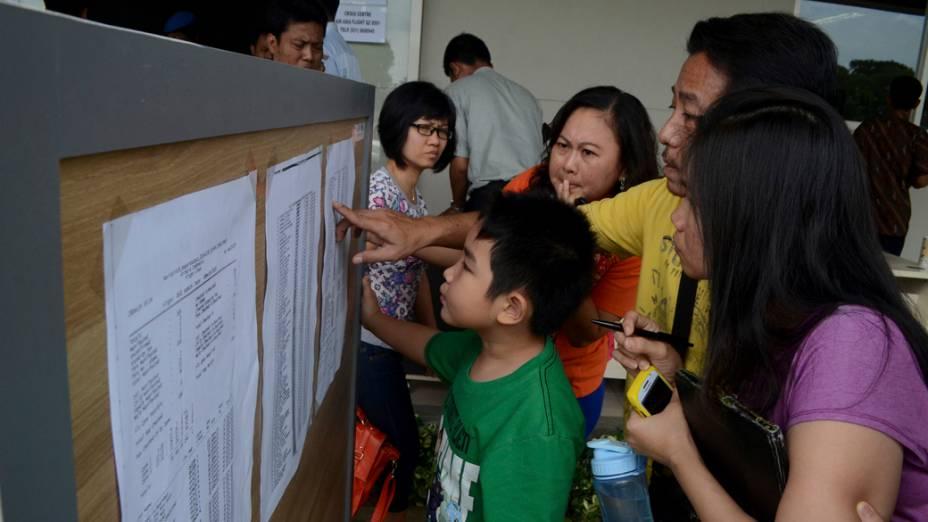 Parentes dos passageiros do voo QZ-8501 da AirAsia conferem lista de ocupantes divulgada no Aeroporto Internacional Juanda, na Indonésia