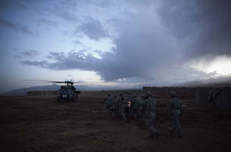 Soldados carregam o corpo do colega morto.