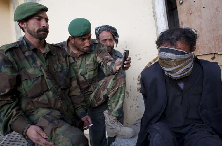 Talibã detido pelas tropas americanas. Foram encontrados em sua casa propaganda pró-talibã, morteiros e munições.