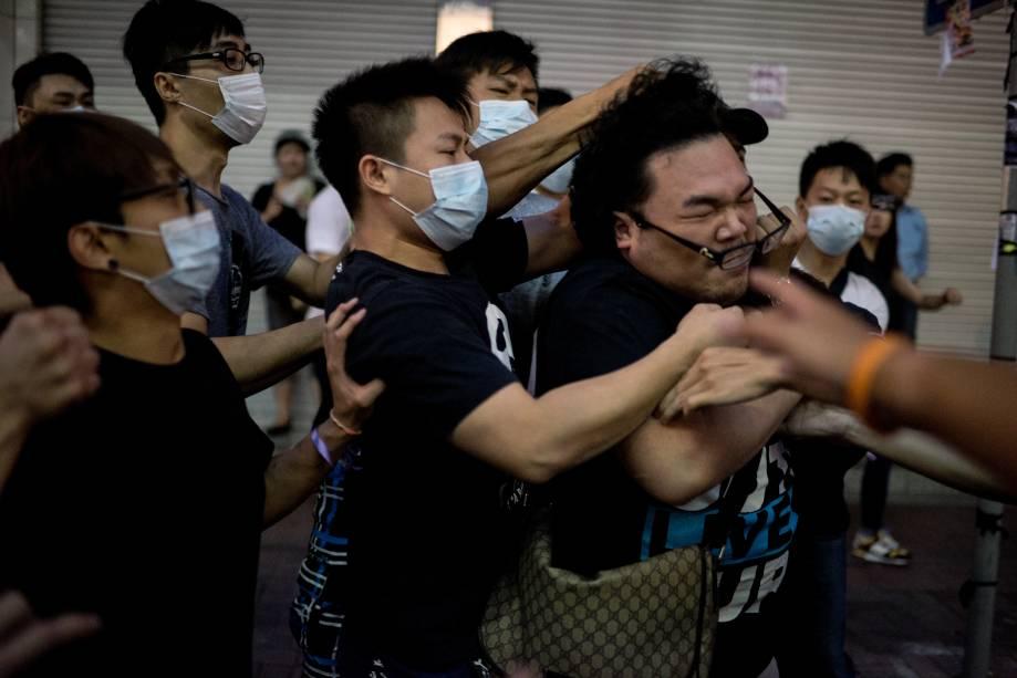 Jovens com máscara batem em homem que tentava impedi-los de remover barricadas de uma área ocupada por manifestantes pró-democracia em Hong Kong. Grupos contrários aos protestos entraram em confronto com os manifestantes