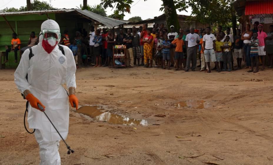 Profissional de saúde da Cruz Vermelha desinfeta local onde corpo de paciente infectado pelo ebola foi encontrado, em 10 de setembro, na Libéria
