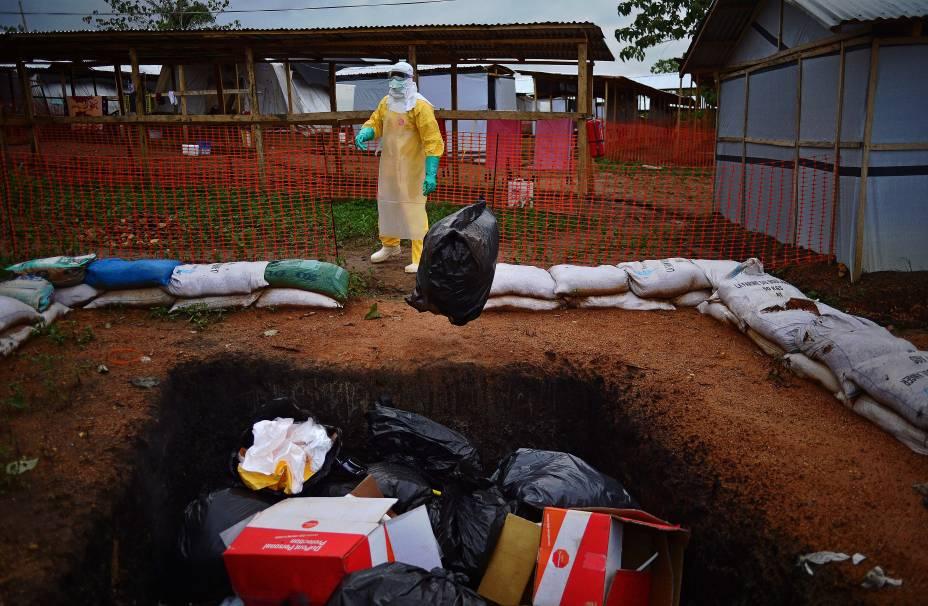 Profissional do Médicos Sem Fronteiras em volta deitens que tiveram contato com infectados pelo ebola momentos antes de serem incinerados em Serra Leoa