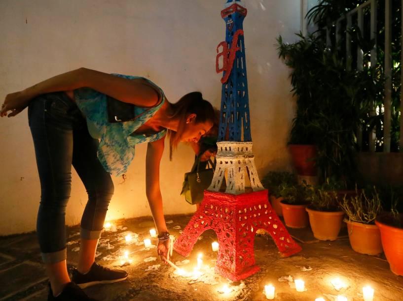 Mulher acende vela em homenagem às vítimas dos ataques terroristas diante de uma réplica da Torre Eiffel em frente a uma unidade da Aliança Francesa em Manila, nas Filipinas
