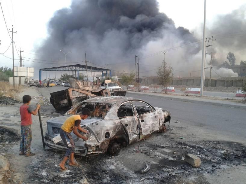 Crianças observam carro destruído após ofensiva dos terroristas do EIIL em Mosul, no Iraque