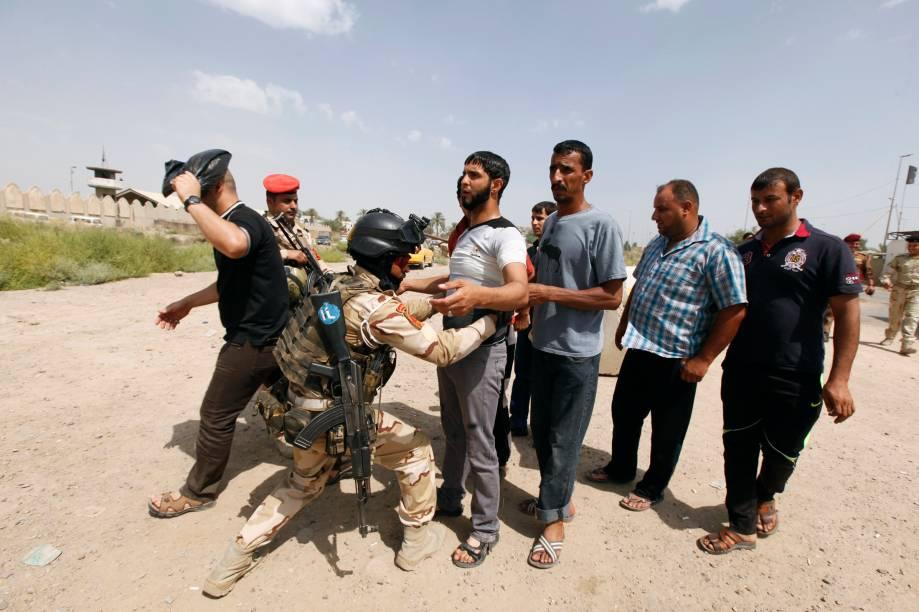 Voluntários são revistados antes de se juntarem ao Exército iraquiano na luta contra os terroristas do EIIL