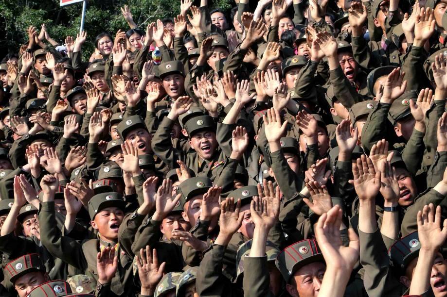 Soldados norte-coreanos acenam durante visita do ditador Kim Jong-un a ilha Ung