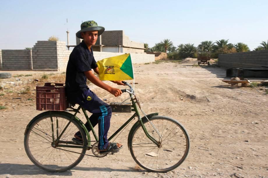 Garoto anda de bicicleta carregando uma bandeira Hezbollah em Amerli, Iraque - 01/09/2014