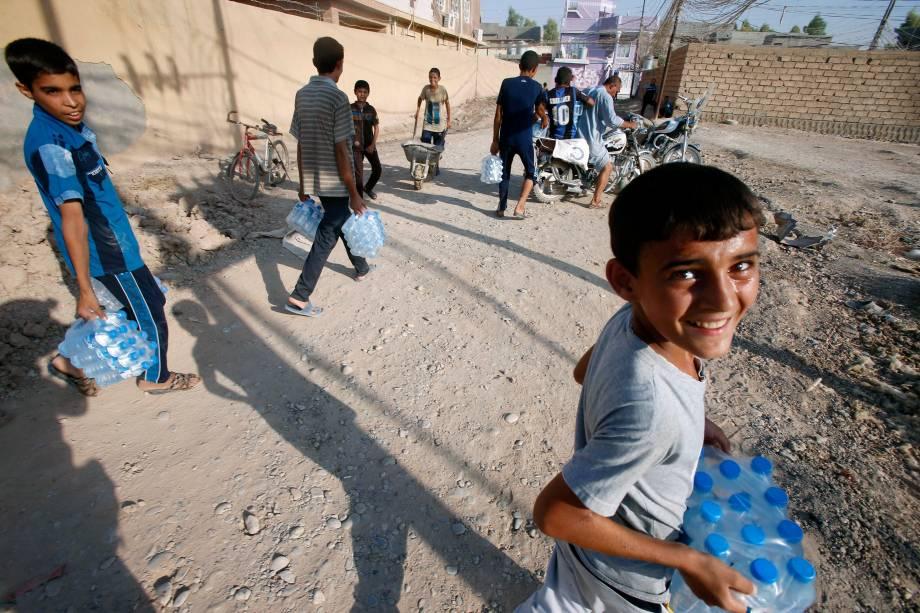 Garotos carregam garrafas de água que receberam de uma doação curda após o rompimento do cerco em Amerli, Iraque - 01/09/2014