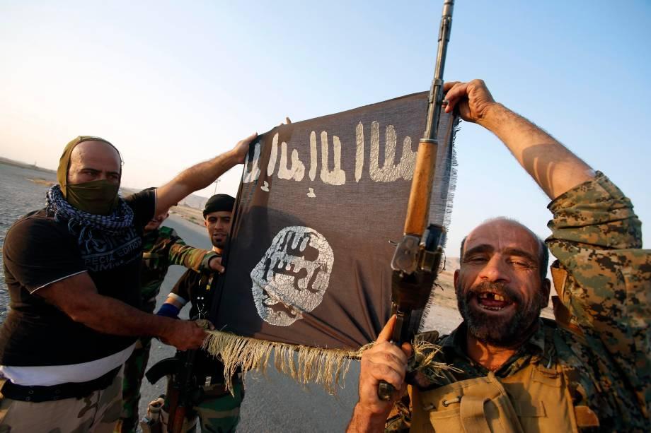 Milícia iraquiana posam com bandeira do Estado Islâmico para celebrar o rompimento do cerco da cidade de Amerli, Iraque - 01/09/2014