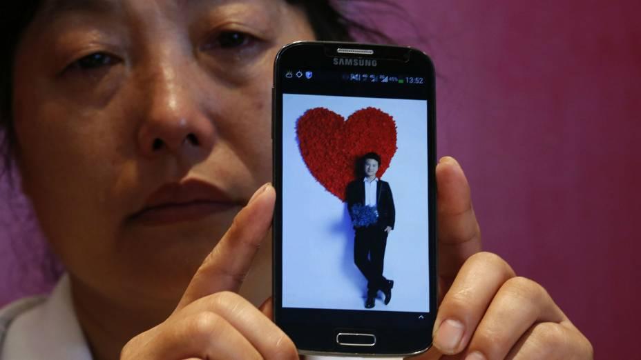 Feng Xuehong, cujo filhoWang Houbin estava a bordo do voo MH370 da Malaysia Airlines, guarda uma foto dele em seu celular