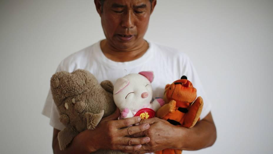 Zhang Yongli segura brinquedos da filhaZhang Qi, que estava a bordo do voo MH370 da Malaysia Airlines