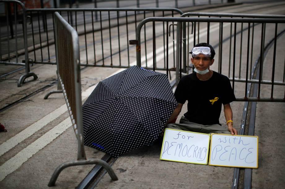 """Homem segura cartazes formando a frase """"pela democracia, com paz"""" durante protesto perto de prédios públicos em Hong Kong"""
