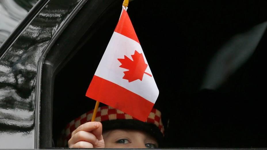 Marcus Cirillo, filho do soldado Nathan, morto no ataque ao Parlamento canadense, carrega uma bandeira do país durante o funeral do pai