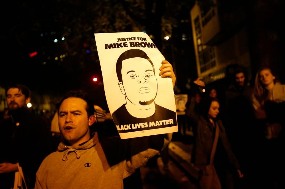 Manifestante levanta cartaz pedindo justiça para Michael Brown, jovem morto por policial no Missouri