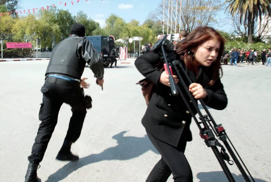 Policial corre do lado de fora do Parlamento de Túnis, na Tunísia. Terroristas atacaram nesta terça-feira o museu nacional, que fica perto do parlamento, deixando mais de 20 mortos