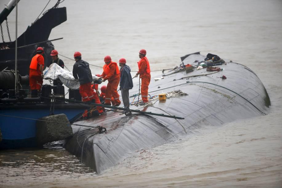 Equipes de resgate retiram um corpo perto de navio naufragado no rio Yang Tsé, na China