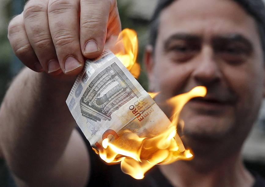 Gregos queimam dinheiro em protesto à restrição de saques nos caixas eletrônicos a 60 euros diários por pessoa