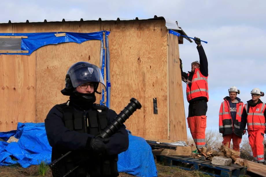 """Guardas e policiais franceses desfazem acampamento de imigrantes que ficou conhecido como """"Selva"""", em Calais, França"""