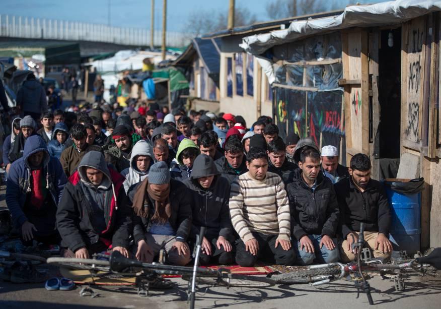 Imigrantes muçulmanos rezam ao lado de acampamento em meio a operação de descupação, em Calais, França. Há anos eles tentam entrar no Reino Unido ilegalmente