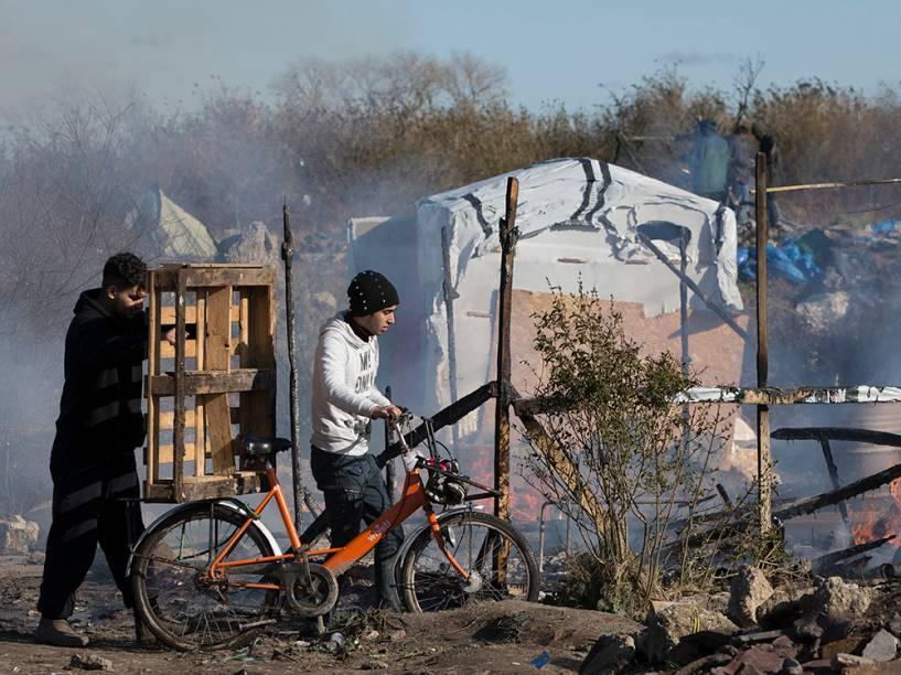 Imigrantes árabes tentam salvar pertences durante operação francesa de desocupação do acampamento ilegal conhecido como ˜Selva˜, em Calais, França