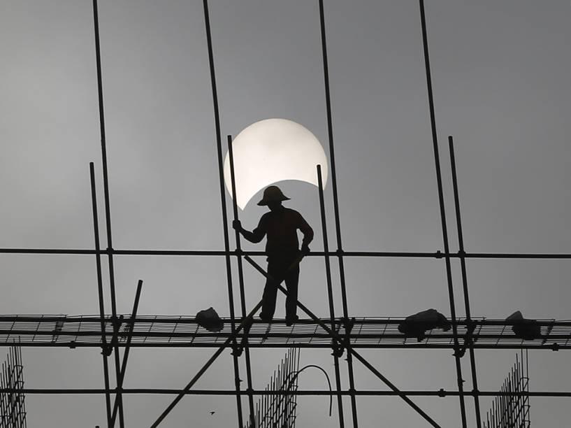 <p>Eclipse solar é visto por trabalhador de construção, no Camboja</p>
