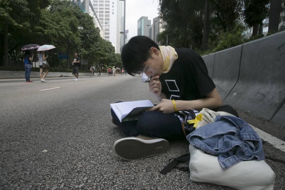 Em uma rua de Hong Kong, estudante aproveita calmaria em meio a protestos para fazer a lição de casa