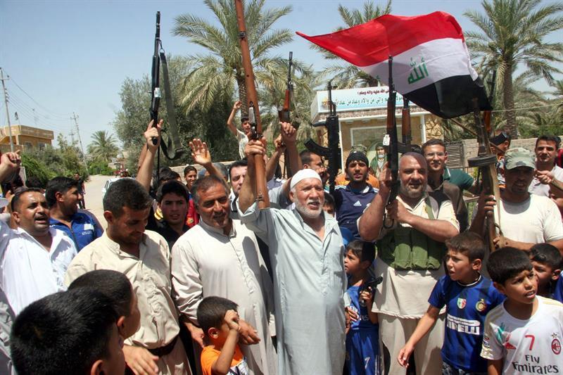 Voluntários iraquianos que se juntaram às forças do Exército comemoram nas ruas de Baquba