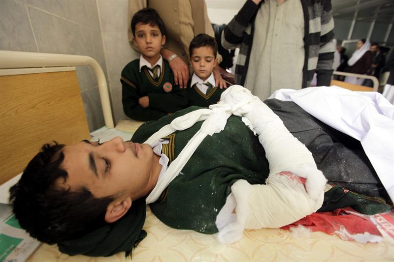 Crianças observam garoto ferido em atentado contra escola no Paquistão