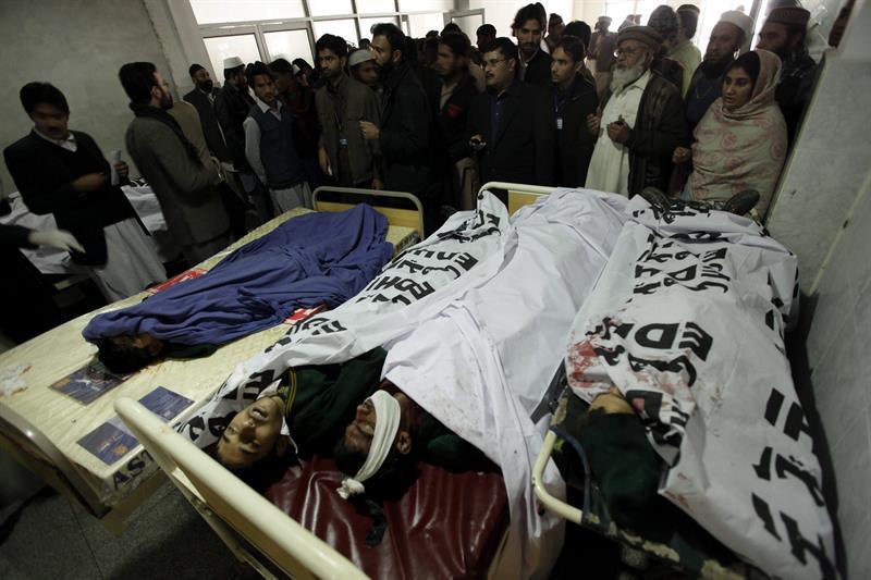 Pessoas observam vítimas do ataque contra uma escola no Paquistão