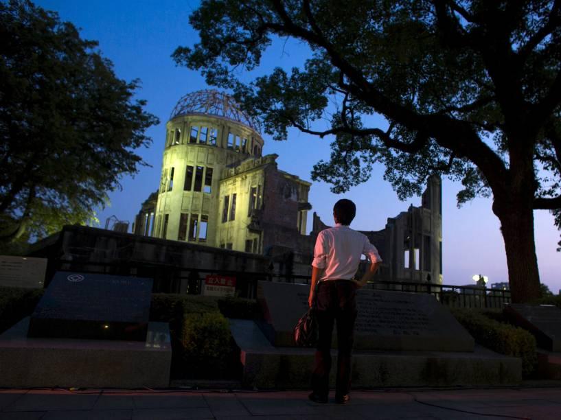 """Homem olha o Domo da Bomba Atômica ao anoitecer em Hiroshima, Japão. O Domo conhecido no japão como """"Genbaku Dome"""", é a única estrutura que continuou em pé neste distrito da cidade, e foi preservado como uma memorial da paz"""