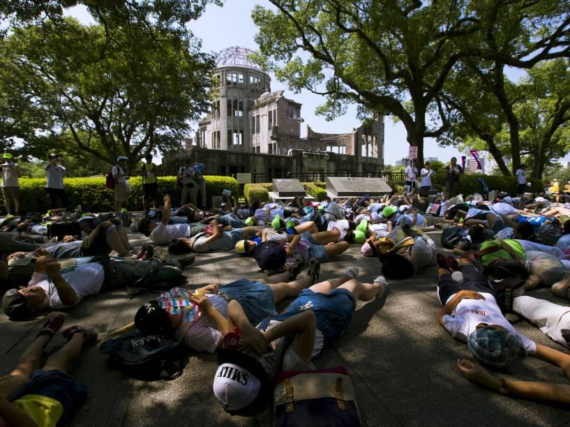 Pessoas deitam no chão fingindo de mortos em frente ao Domo da Bomba Atômica, em ato em lembrança às vítimas da bomba que atingiu Hiroshima em 1945, matando cerca de 140 mil pessoas