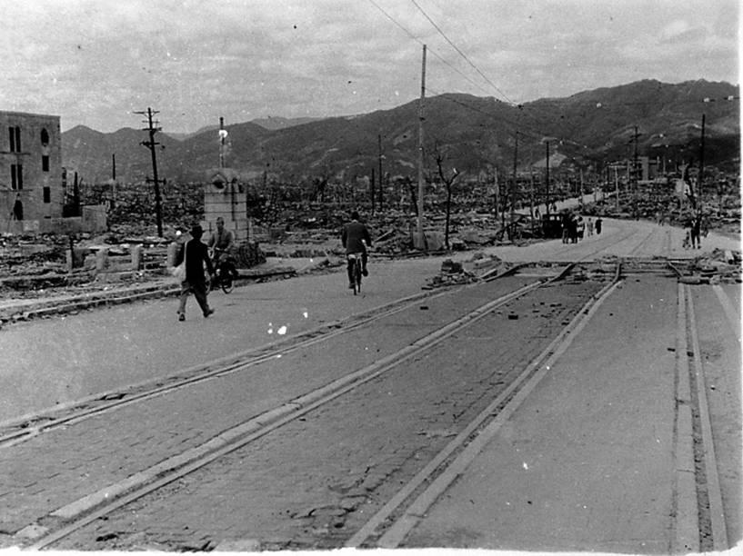 Moradores caminham em frente a prédios destruidos próximo à ponte Aioi, em Hiroshima, após o ataque nuclear à cidade no dia 6 de Agosto de 1945