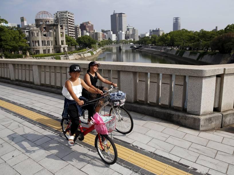 Crianças andam de bicicleta na ponte Aioi, com o Domo da Bomba Atômica ao fundo, em Hiroshima, Japão. No dia 6 de agosto de 1945, os Estados Unidos soltaram a bomba atômica na cidade, matando cerca de 140 mil dos 350 mil residentes de Hiroshima, no primeiro ataque nuclear da história. Três dias depois, uma segunda bomba foi jogada em Nagasaki
