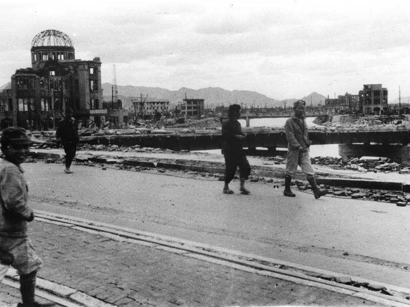 Moradores passam em frente ao Palácio das Indústrias de Hiroshima, hoje conhecido como Domo da Bomba Atômica, na ponte Aioi, após o ataque contra Hiroshima no dia 6 de agosto de 1945