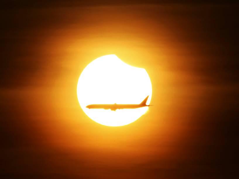 <p>Avião comercial passa enquanto acontece o eclipse solar parcial em Cingapura, nesta quarta-feira (09)</p>