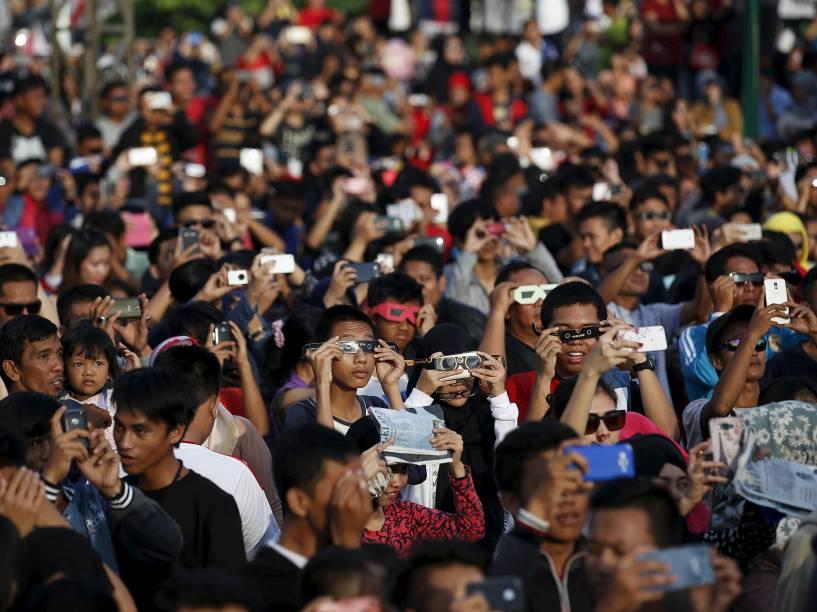 <p>Pessoas usam óculos para acompanhar o eclipse total do Sol perto da ponte Ampera ao longo das margens do rio Musi em Palembang, na província de Sumatra do Sul, Indonésia</p>