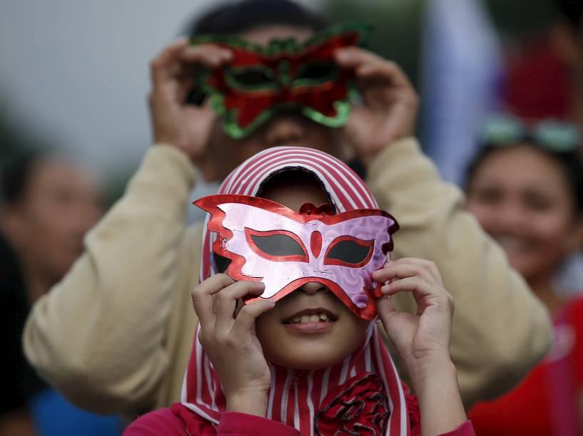 <p>Jovens usam óculos para acompanhar o eclipse total do Sol perto da ponte Ampera ao longo das margens do rio Musi em Palembang, na província de Sumatra do Sul, Indonésia</p>