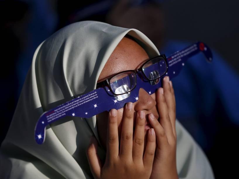 <p>Garota observa o eclipse solar total visto a partir da cidade de Kuala Lumpur, capital da Malásia</p>