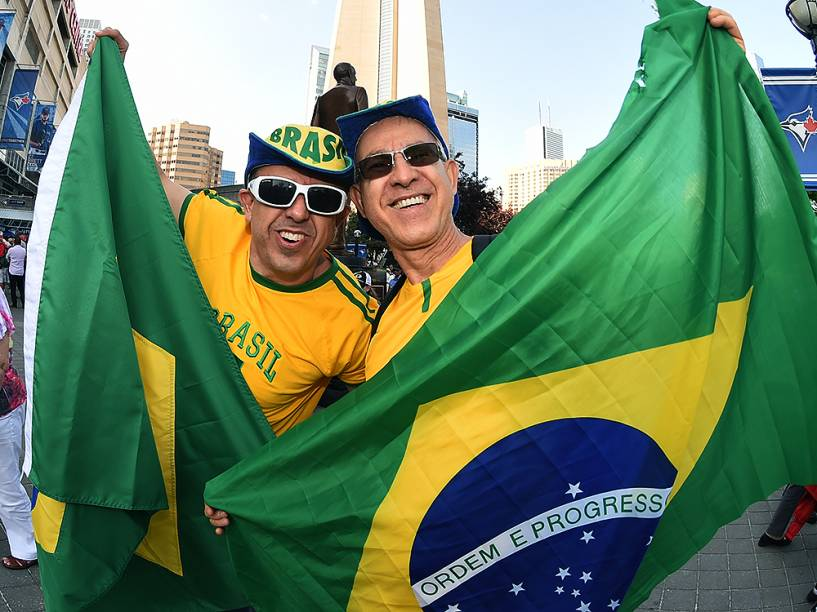 Brasileiros carregam a bandeira do país enquanto seguem em direção ao Rogers Centre em Toronto para a cerimônia de abertura dos Jogos Pan-Americanos 2015