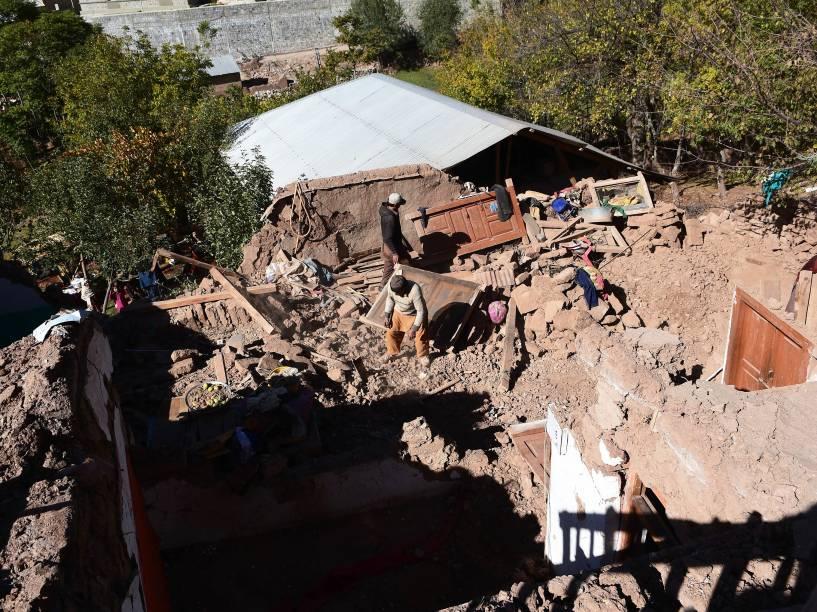 Sobreviventes de terremoto que atingiu o Paquistão retiram seus pertences em meio aos destroços de casas destruídas
